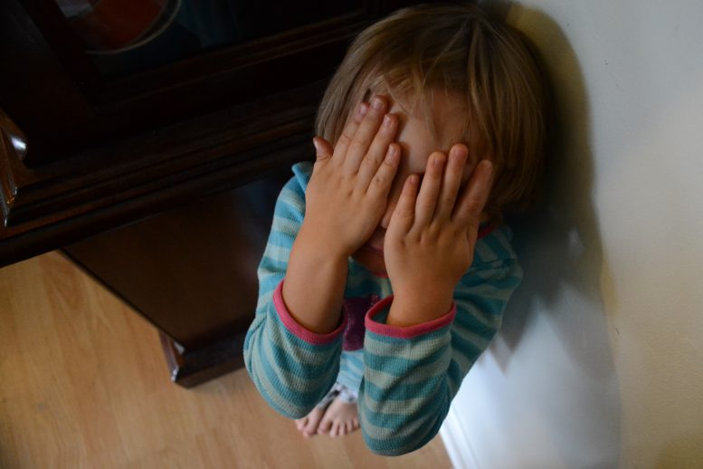Little girl hides in corner with hands over her eyes