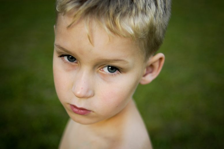 Portrait of serious little boy with green background