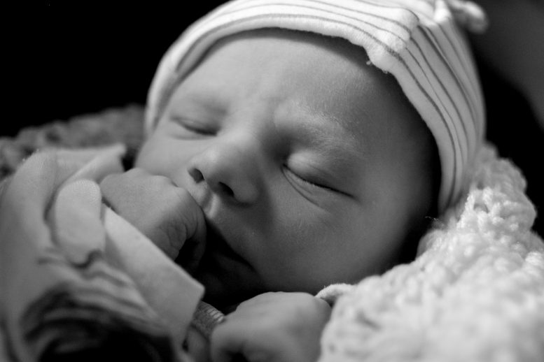 Newborn with hand up to his mouth