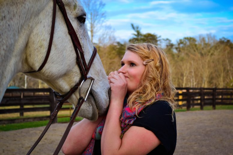 Photo of young woman with her horse