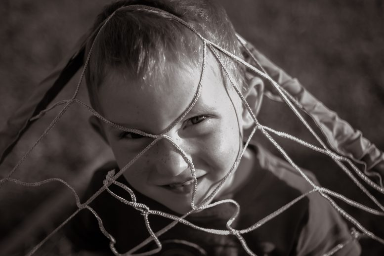 Photo of little boy looking through soccer net