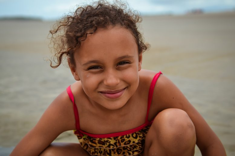 Smiling girl on beach with wind blowing her curly hair