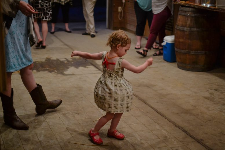 Photo of little girl dancing in bright pink shoes
