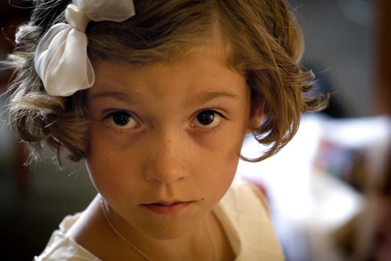 Close-up photo of serious little girl with white bow in her hair